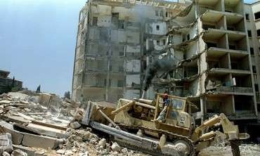 A bulldozer demolishes August 7 the bombed out building of the American embassy in Beirut. The embas..