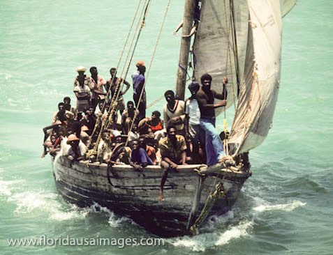 Photograph of Haitian refugees in small wood boats sailing into Biscayne Bay, Miami, Florida attempting to immigrate into the United States.