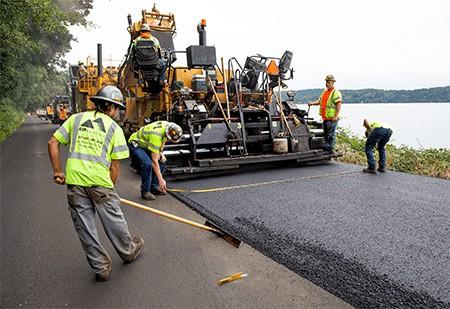 Construction workers lay new asphalt (2018). Kingcounty.gov