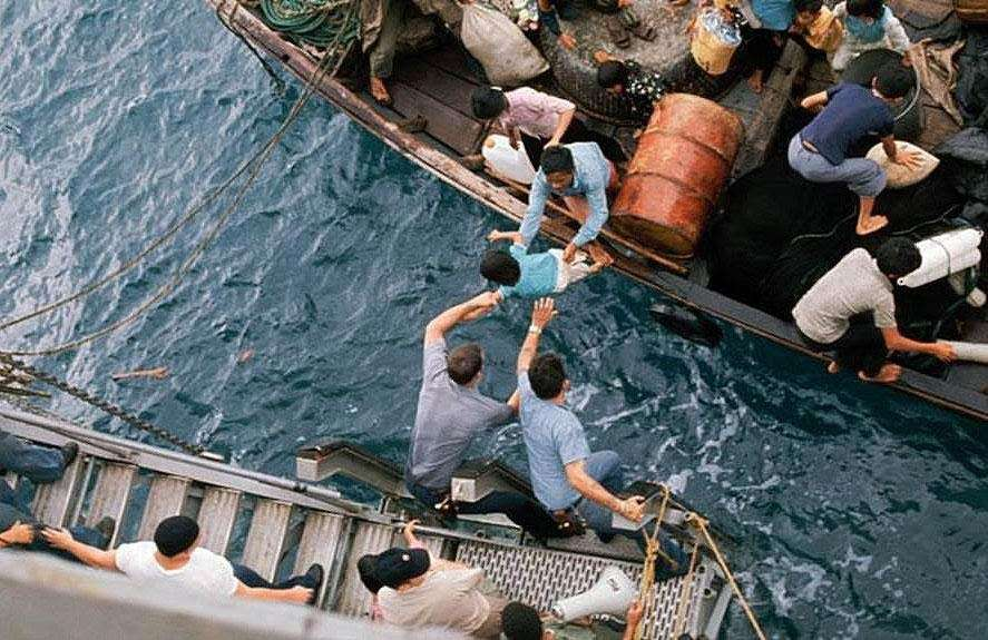U.S government personnel help transfer refugees from a barge to a Navy ship |  U.S Navy Archives
