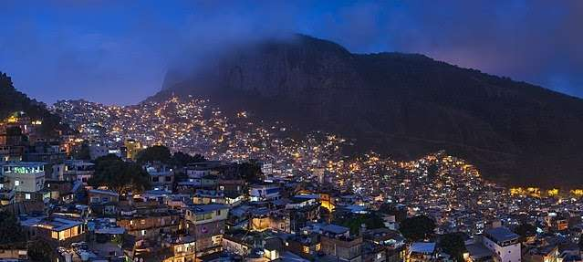 Panorama at night of Rocinha, the largest favela in Brazil, in Rio de Janeiro city, with the Morro Dois Irmãos (Two Brothers Hill) in the background, in June 2014 | Wikimedia